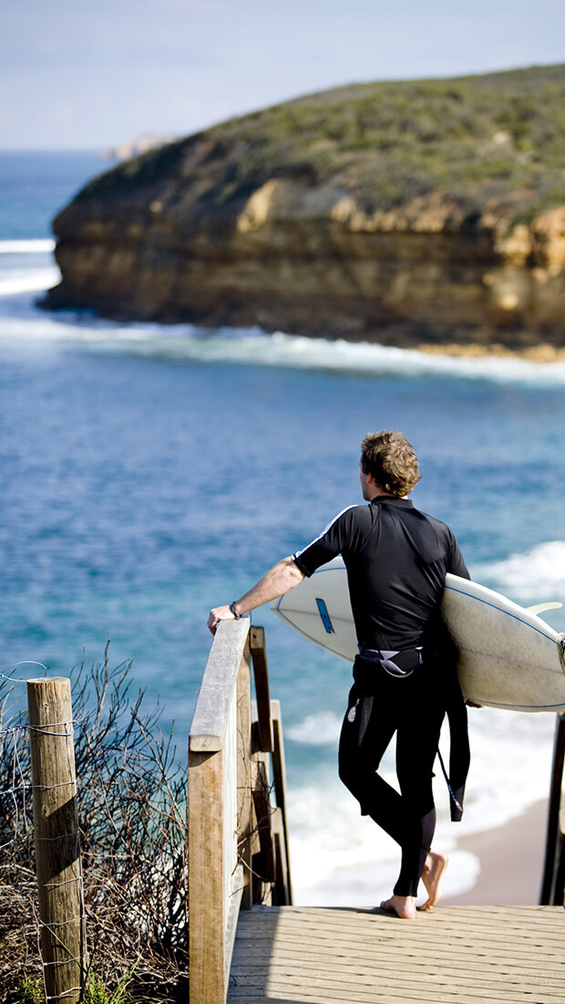 Trip to Australia - Man at the Melbourne beach with a surf board