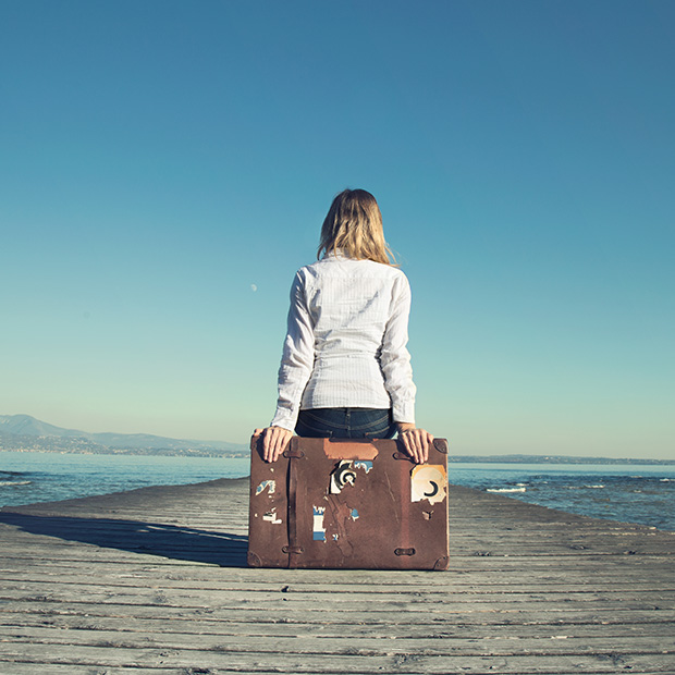 woman sitting on a suitcase looking outward