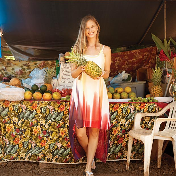 woman holding a pineapple by a fruit stand