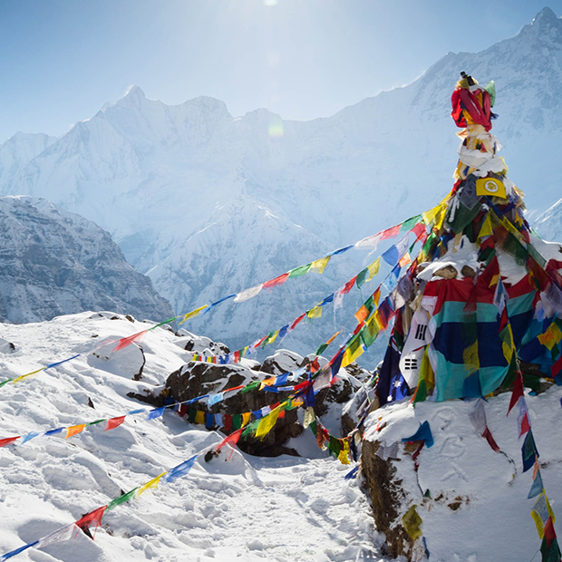 snowy mountains covered in colourful flags in himalayas