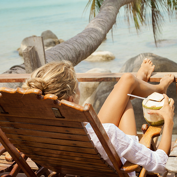 wellness-travel-woman-drinking-from-coconut-reclined-on-beach-deck