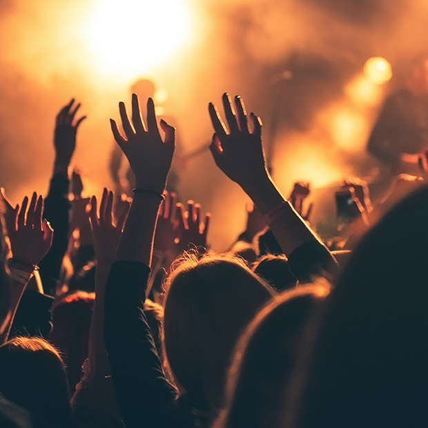 concert or music festival audience at night with hands in the air