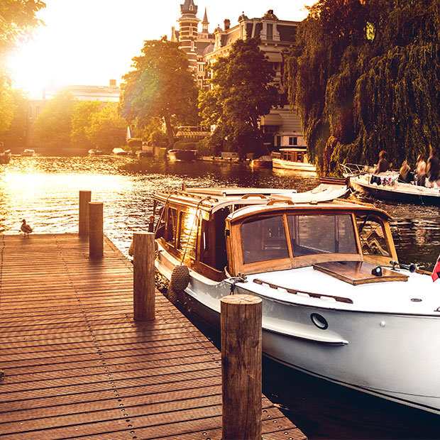 boat docked at sunset along amsterdam canal