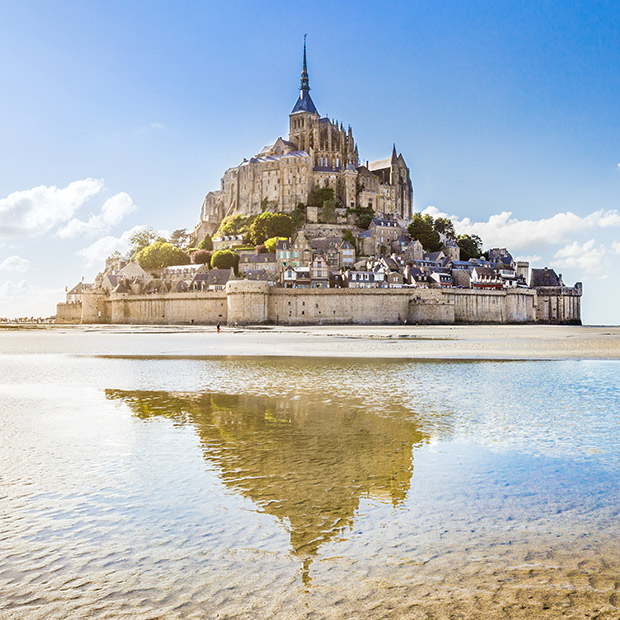 normandy castle france on a blue sky day with reflection on water