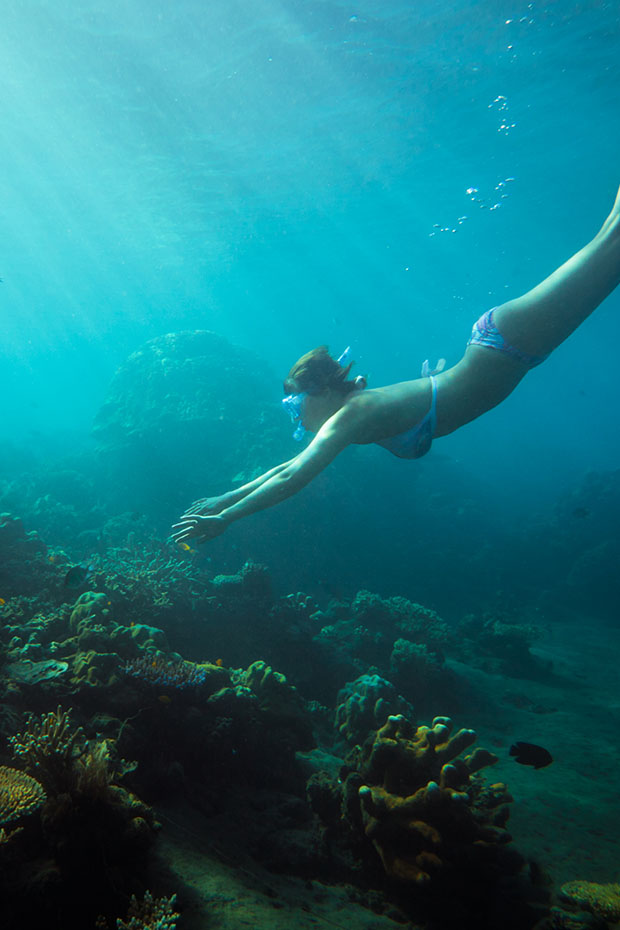woman snorkelling by reef in fiji