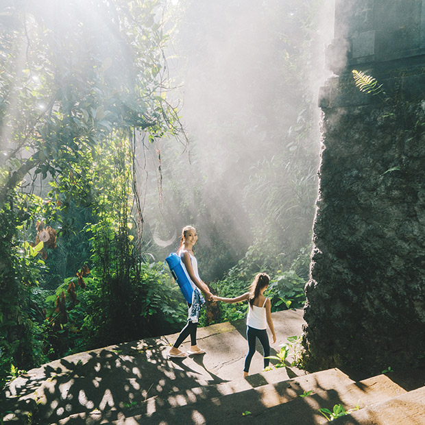 yoga-retreat-things-to-do-bali-mom--daughter-handholding-scenic-backdrop-trees