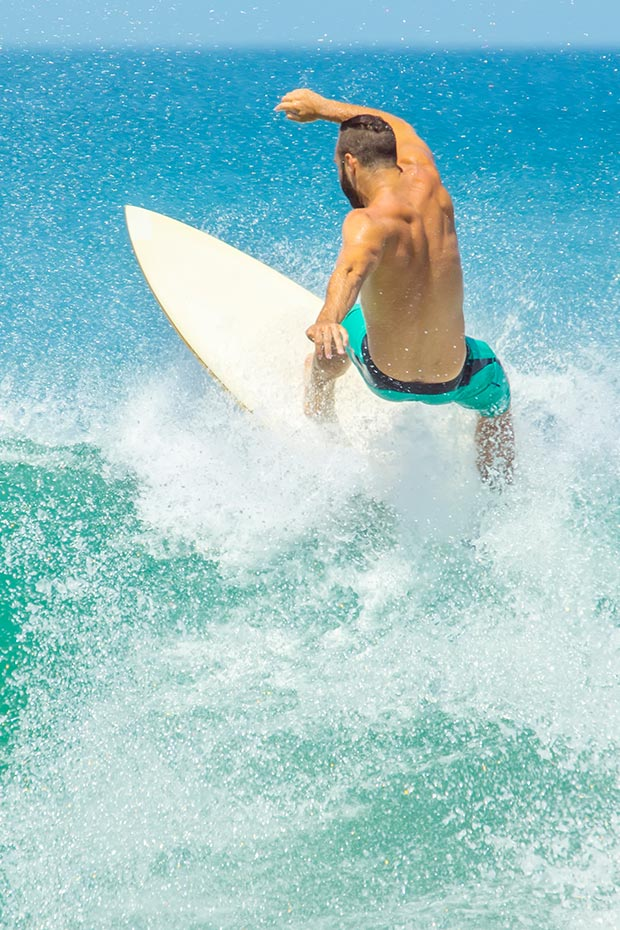 costa-rica-beaches-male-surfer-rides-a-wave-at-playa-langosta
