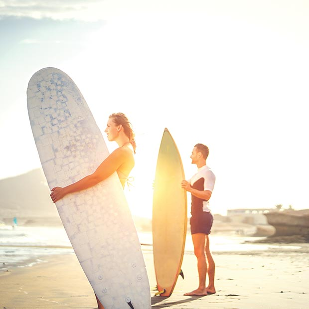 couple holding surf boards on the beach