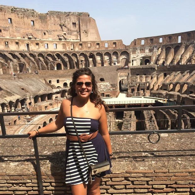 young-woman-in-striped-dress-stands-in-front-of-colosseum-rome-italy