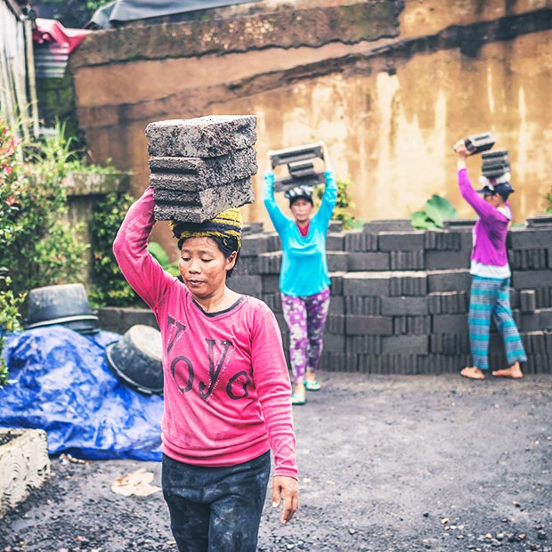 asian-women-in-developing-country-carry-large-stone-bricks-on-their-heads