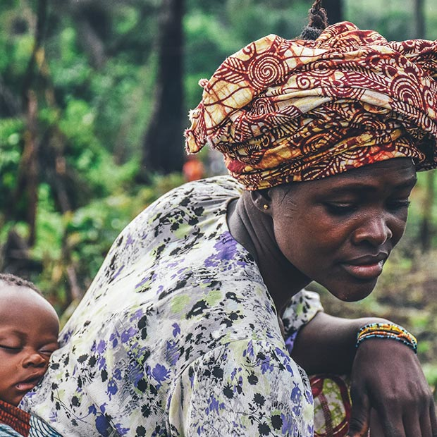 african-woman-kneels-doing-farming-work-with-cute-baby-on-her-back