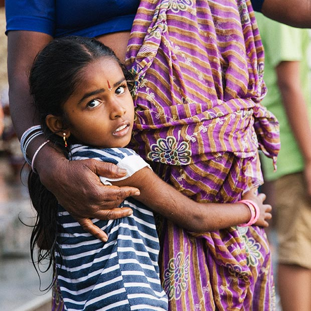young-indian-girl-embraces-mother-wearing-traditional-sari