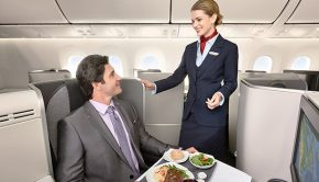 business class cabin female flight attendant serves male business traveller