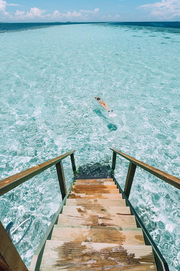 woman swimming near overwater bungalow