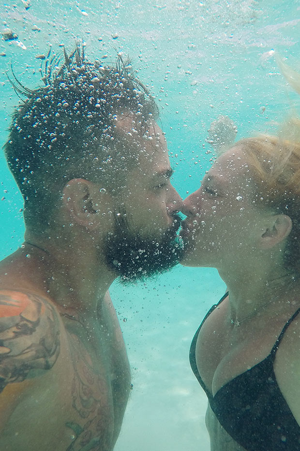 man and woman kissing under the water