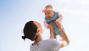 mother-holds-smiling-baby-girl-up-in-the-air