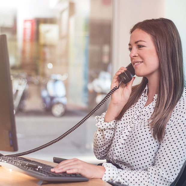 flight centre business travel expert woman helps client on the phone book travel