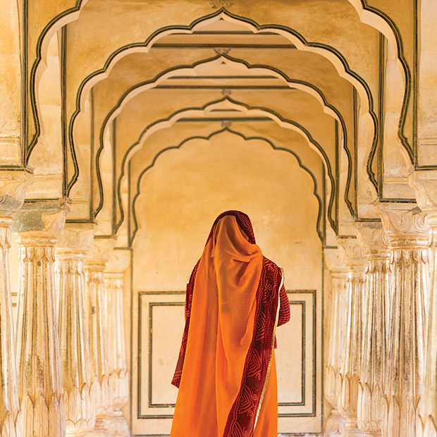 woman walking through archways in india