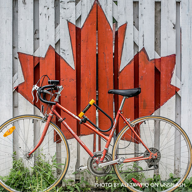 bike leaning against a fence with a maple leaf on it