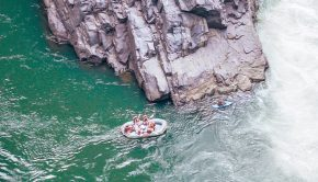 people in a boat beside a cliff and waterfall