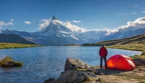 man standing by a tent looking at a lake and a mountain