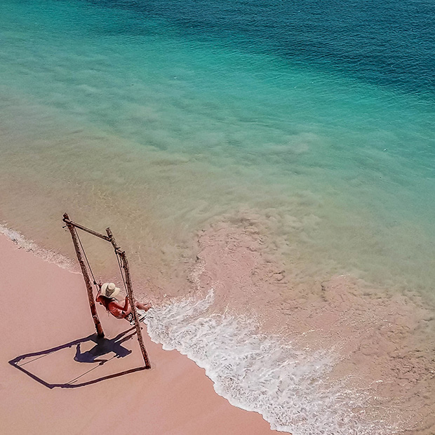 Girl on beach swing in Bali