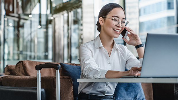 business woman talks on the phone while working in an airport business class lounge