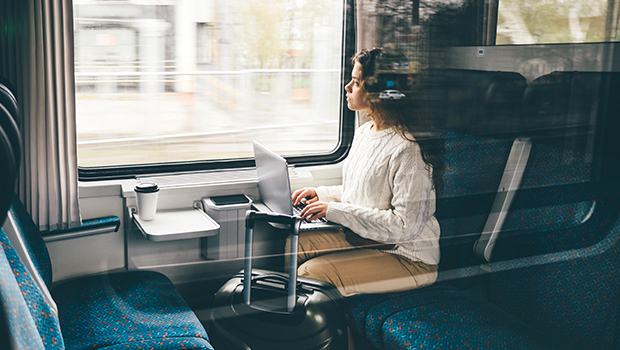 woman with a laptop looks out the window of a train