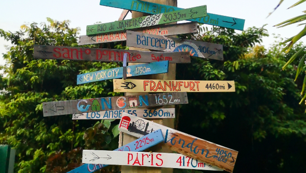 a wooden sign points to capitals around the world