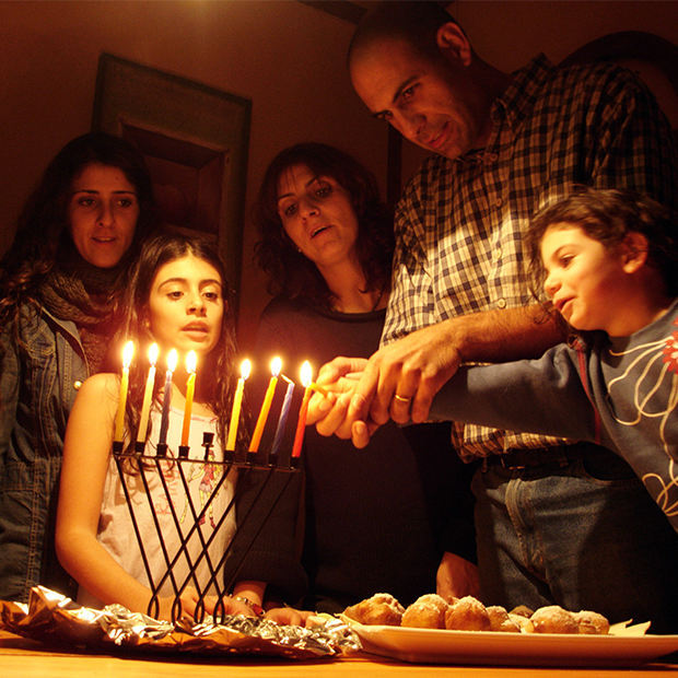 a family gathers to light the candles of a menorah for hanukkah celebrations in yemen