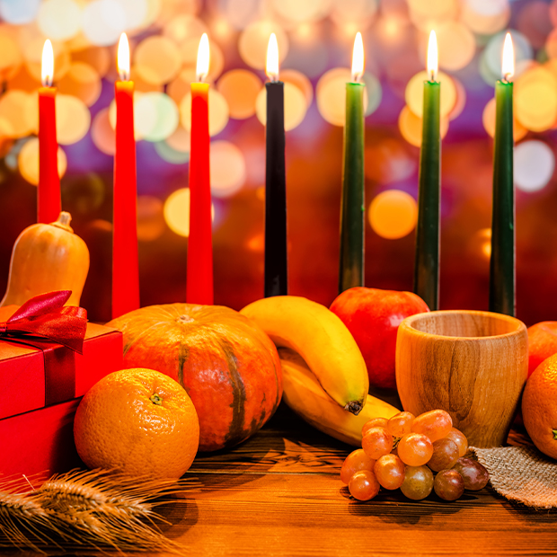 seven candles are lit surrounded by other kwanzaa symbols like fruit gifts and kwanzaa mat