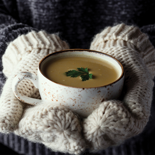 a woman with mittens on holds a cup of hot soup