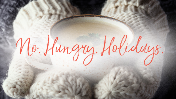 a person with mittens on holds a hot cup of soup