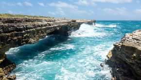 big waves crash against devil's bridge rock formation in antigua