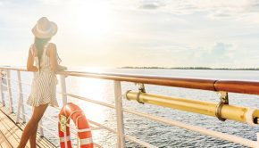 woman looks out over side of cruise ship towards ocean