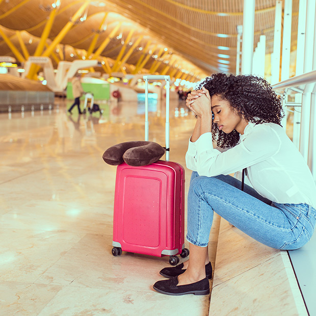 frustrated traveller sitting in the airport with her luggage