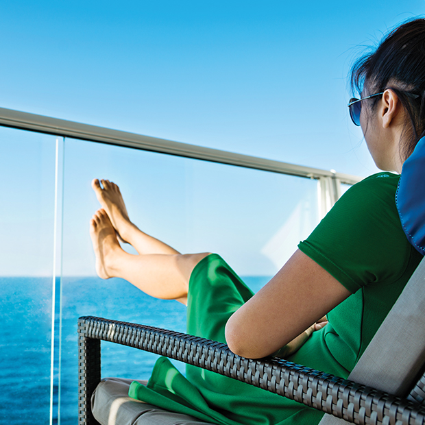 young traveller puts her feet up on the balcony of a cruise ship