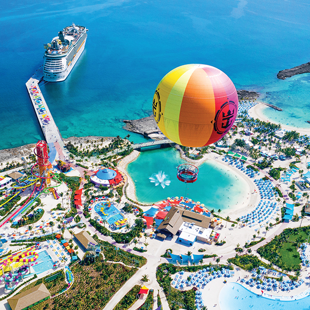 giant helium balloon floats above colourful water park with royal caribbean cruise ship in background