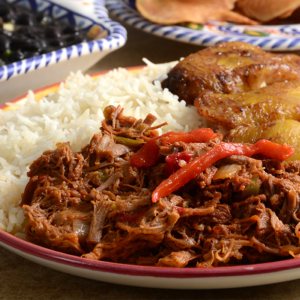 ropa vieja on a plate served with rice and fried plantain