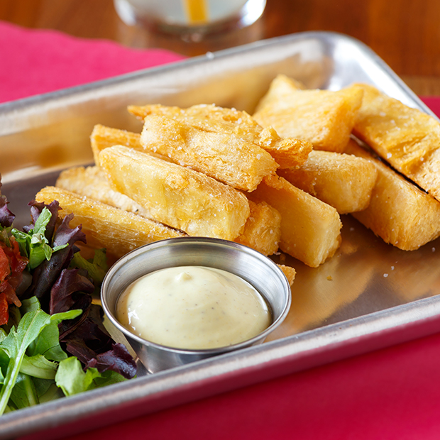 yuca fries with dip on a serving platter
