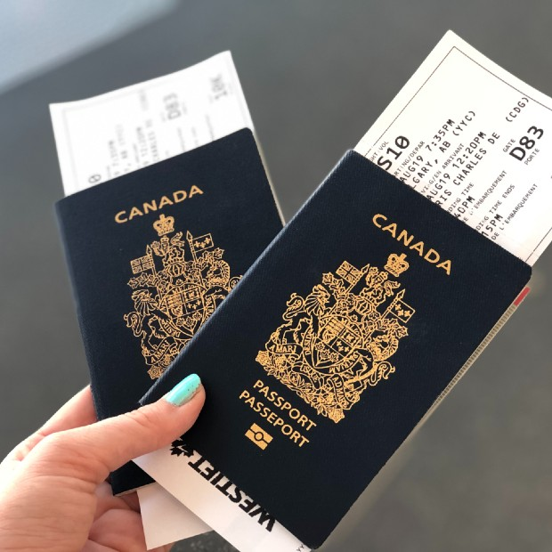 business traveller holding two canadian passport with boarding passes in her hands