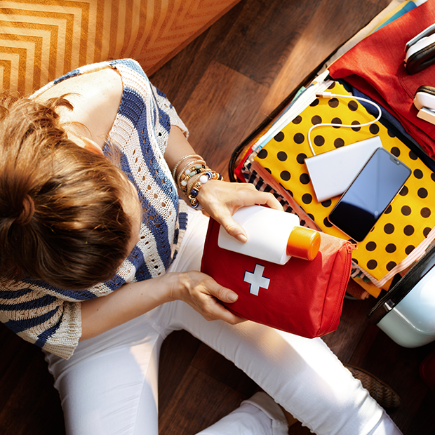 a woman packs a travelling first aid kit into her suitcase