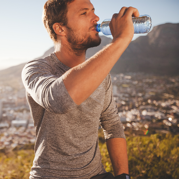 a man drinks bottled water while hiking