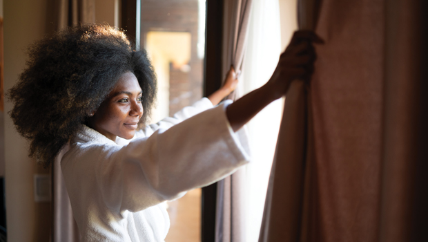 woman smiling and looking out the window as she opens the curtains in her hotel room