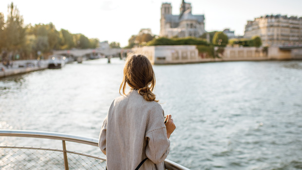 Woman looking out over the Seine from a cruise