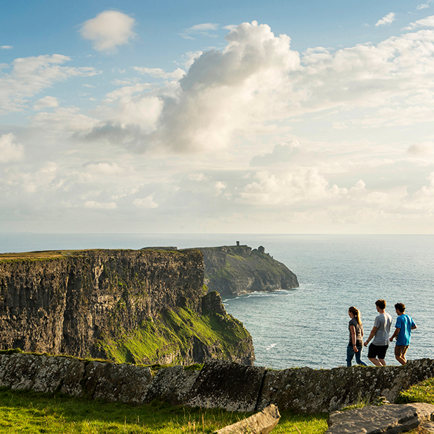 three travellers enjoy a clifftop hike on a sunny day