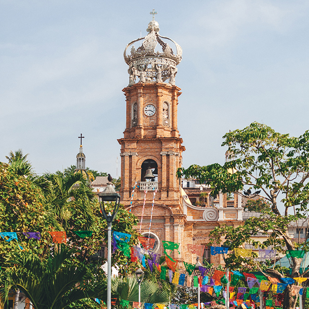 ornate bell tower surrounded by trees and colourful flags in mexico