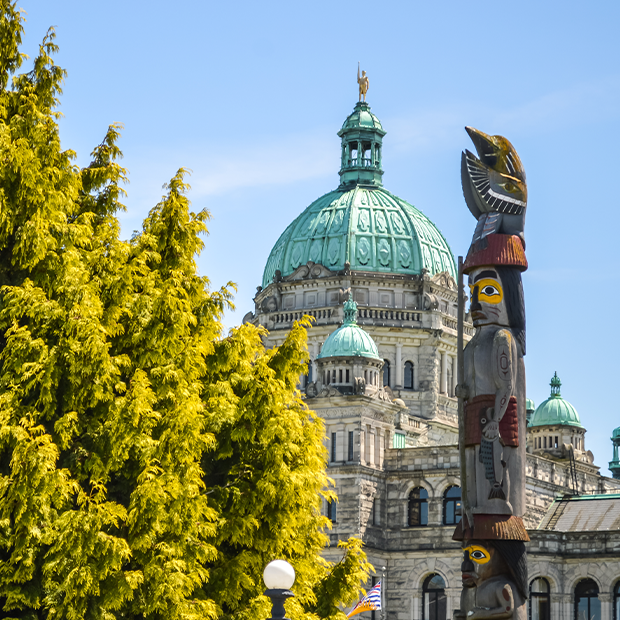 british columbia parliamentary buildings in victoria and a totem pole in the foreground