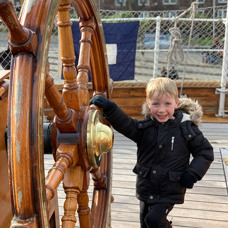 child smiles beside wheel of cutty sark ship