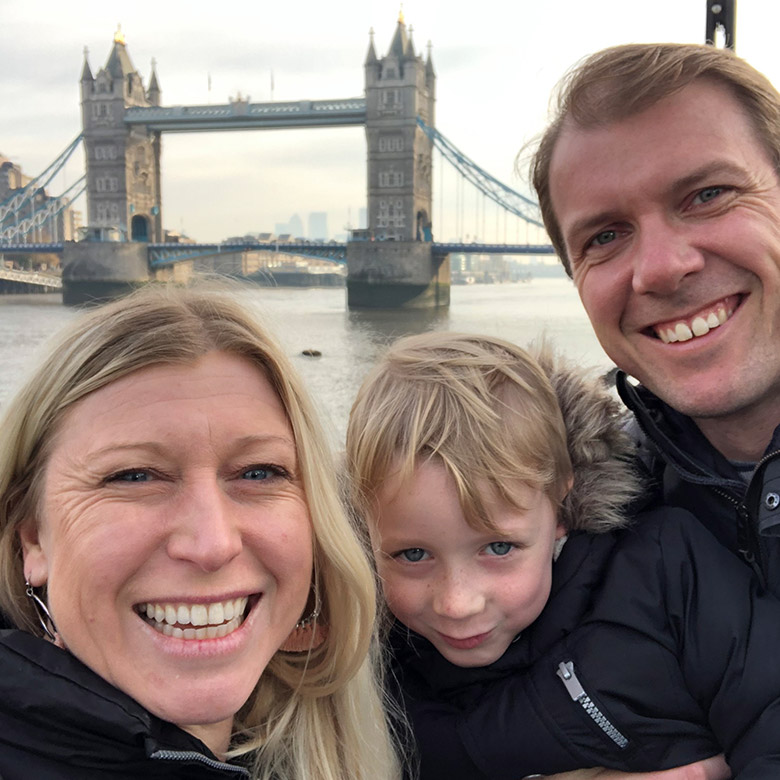a family smiles with tower bridge in background